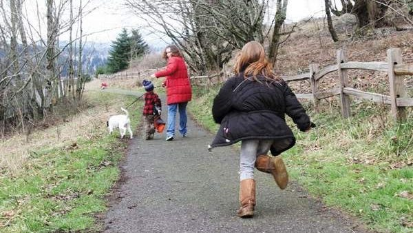 Kayla Kimber scurries toward her family. Powell Butte Nature Park consists of nearly 600 acres of hiking trails and meadows atop an extinct volcano in Southeast Portland.