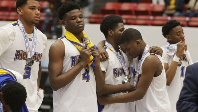 Rickards basketball players react to being awarded silver medals as Class 6A state runner-up after falling 71-62 to Leesburg in the championship game Friday night in Lakeland.