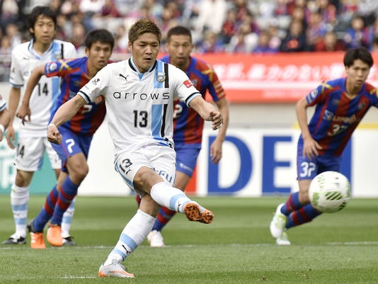 In this Saturday, April 16, 2016 photo, Kawasaki Frontale's Yoshito Okubo (13) scores on a penalty kick against FC Tokyo in their J-League soccer match in Kawasaki, near Tokyo. It's his 161st career goal. Veteren striker Okubo is making a case for inclusion in Japan's national team while re-writing the J-League record books. Okubo scored his record-extending 160th and 161st career goals in the match to lead first-place Kawasaki to a 4-2 win over FC Tokyo. The 33-year-old Okubo now has five goals in seven games, a pace that has caught the attention of Japan coach Vahid Halilhodzic. (Kyodo News via AP) JAPAN OUT, MANDATORY CREDIT