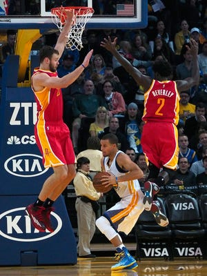 Golden State Warriors guard Stephen Curry fakes a shot as Houston Rockets forward Donatas Motiejunas (L) guard Patrick Beverley (R) defend during the first half at Oracle Arena in Oakland on December 10, 2014.