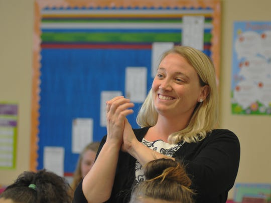 6th grade teacher Nicole Hodkinson, seen her applauding a presentation by members of her class at Imagine Schools at West Melbourne. Her students created presentations on seven key issues that Presidential candidates are facing: The economy, immigration, terrorism, climate change, gun control, education, and health care.