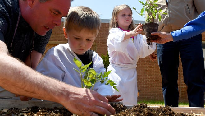 A member of the Staunton Rotary Club, Frank Strassler helps preschooler Cameron Mavis with planting a plant in one of the raised beds as preschooler Makalyn Lyle is handed a plant of her own to plant. The new Dixon Green Lab garden was dedicated at the Dixon Educational Center on Tuesday, April 21, 2015