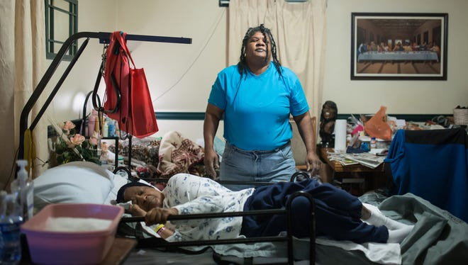 Lisa Gaines of Flint slowly stands up after the long process of cleaning and dressing Erma Jean Gaines, her 70-year-old bedridden mother, in the dining room of their home.