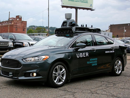 A self-driving Uber car drives down River Road on Pittsburgh's