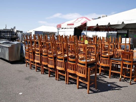 Restaurant stools are stacked outside of SAM Auctions.
