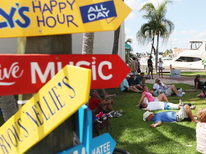 Visitors to Fort Myers Beach relax on the lawn while