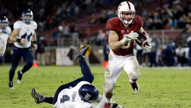 Stanford running back Christian McCaffrey, right, runs past Rice linebacker Alex Lyons on a 23-yard touchdown reception during the first half of their NCAA college football game Nov. 26 in Stanford, Calif.