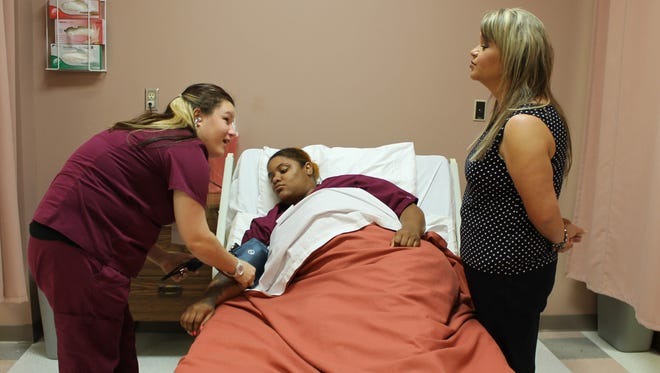 Certified nursing assistant student Brittany Marlborough of Picayune asks instructor Sandra Culpepper a question as she takes the blood pressure of fellow student Quannetia Lockhart of Hattiesburg. The women have completed the 12-week course at Pearl River Community College and will take state certification exams in December.
