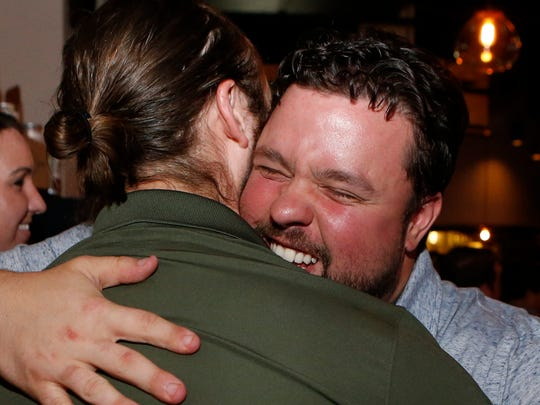 Stone Balloon Ale House chef Robbie Jester (facing camera) shares a congratulatory hug with Sean Riley, a manager, after watching himself beat Bobby Flay on the Food Network show of the same name during a viewing gathering at the Newark restaurant.
