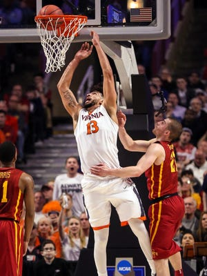 Virginia's Anthony Gill dunks the ball as Iowa State's Matt Thomas (21) defends in the regional semifinals of the men's NCAA Tournament, in Chicago Friday, March 25, 2016.