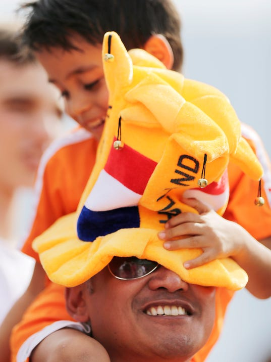 A young fan of the Netherlands soccer team sits on his father's shoulders as they watch from the stands during a training session in Rio de Janeiro, Brazil, Saturday, June 7, 2014. The Netherlands had their first training session open to fans at the Brazilian club Flamengo training complex. The Netherlands plays in group B of the 2014 soccer World Cup. (AP Photo/Wong Maye-E)