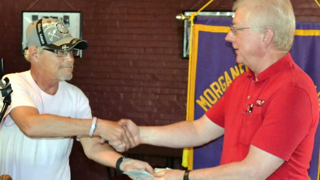 Billy O'Leary, left presents a donation to Morganfield Lions Club President Darrel Huff at a recent Lions' luncheon meeting.  The donation was some $500--the proceeds from a May car show.  The donation will be used for eye care.