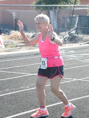 Dottie Gray raises her arms after crossing the finish line on the track at Snow Canyon High School during Huntsman World Senior Games competition Wednesday, Oct. 7, 2015.