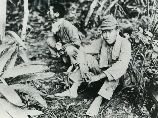 Tow Japanese soldiers who were captured during the liberation of Guam wait for their fate to be determined.