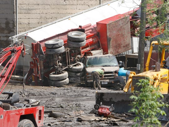 Twisted and mud-covered trucks are a testament to the impact of the May floods along Elm Street in Penn Yan, leaving plenty of cleanup work for residents and volunteers.