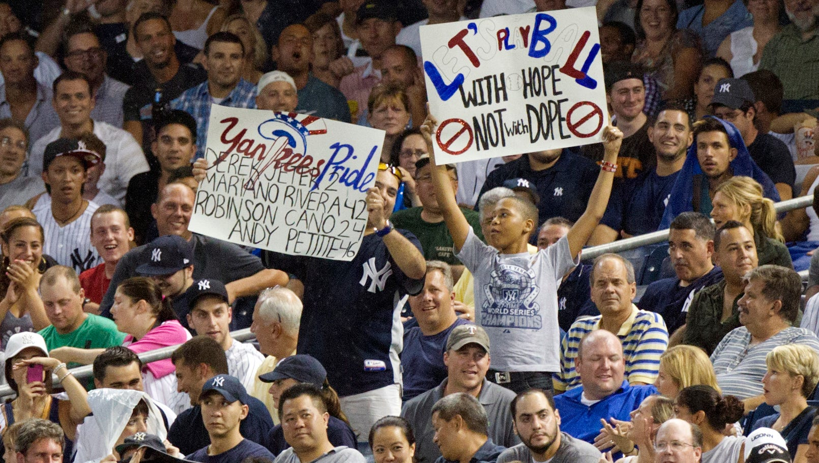 Fans hold signs as New York Yankees third baseman Alex Rodriguez comes to bat during the first inning against the Detroit Tigers at Yankee Stadium.