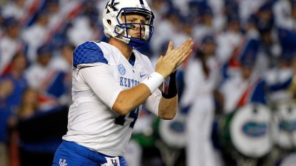 Kentucky Wildcats quarterback Patrick Towles (14) claps during the first quarter against the Florida Gators at Ben Hill Griffin Stadium.