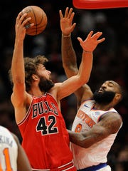 Chicago Bulls' Robin Lopez (42) goes up to shoot against New York Knicks' Kyle O'Quinn (9) during the first half of an NBA basketball game Wednesday, Dec. 27, 2017, in Chicago.