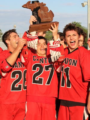 Canton hero Zach Sweet (27) hoists the regional trophy with assistance from teammates Steven Szymusiak (26) and Connor Flannigan (11).