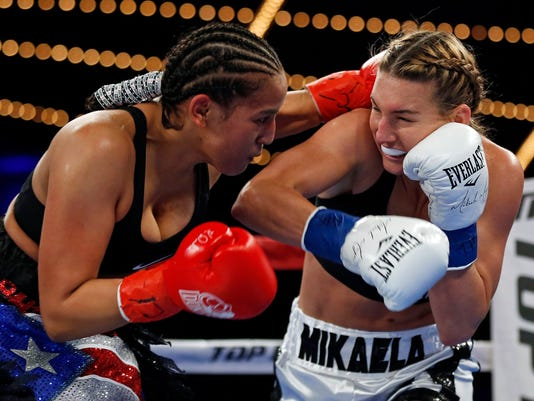 Mikaela Mayer, right, punches Nydia Feliciano during the first round of a lightweight boxing match Saturday, Dec. 9, 2017, in New York. (AP Photo/Adam Hunger)