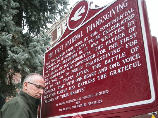 Judicial Center Facilities Manager Vada Fink, tightens the last screw on the First National Thanksgiving marker, near 21 E. Market Street Tuesday, Nov. 1, 2016, in York City. An anonymous donor had the York City First National Thanksgiving marker sanded and repainted. Amanda J. Cain photo
