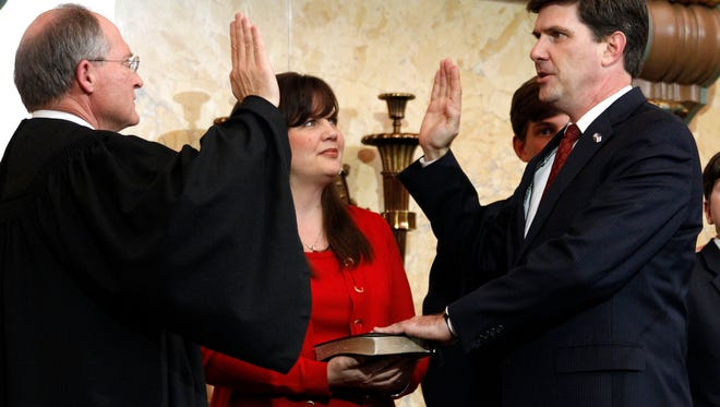 In this 2012 file photo, State Auditor Stacey Pickering recites the oath of office as spoken by Mississippi Supreme Court Chief Justice William Waller Jr., left, while his wife Whitney Pickering holds the Bible.