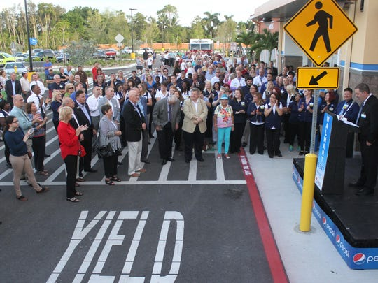 Visitors to the new Village of Estero Wal-Mart crowd around the entrance as Wal-Mart manager Brooks McGhee speaks during the grand opening on Wednesday morning.
