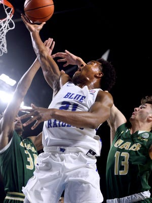 MTSU's David Simmons (21) goes up for a shot as UAB's William Lee (34) and Nate Darling (13) defend him on Saturday.