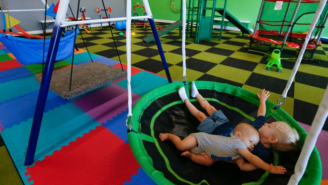 Jayden Witt, 3, and his brother Kasen, 11-months, play on a swing as at the Jungle Gym, an indoor 'sensory play' environment for kids on Monday, July 16, 2018.