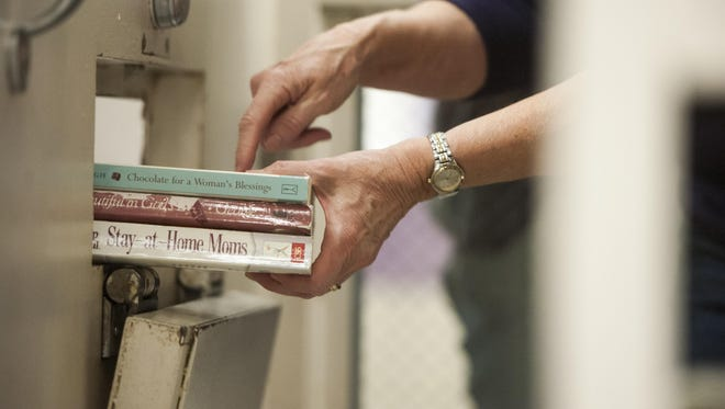 Volunteer Mary Lou Norbie hands a selection of books to female inmates through a small port in the door at the Cascade County Detention Center.