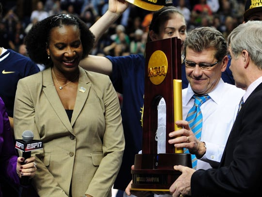 Battle Creek native Carolayne Henry watches as Connecticut Huskies head coach Geno Auriemma receives the 2014 championship trophy .