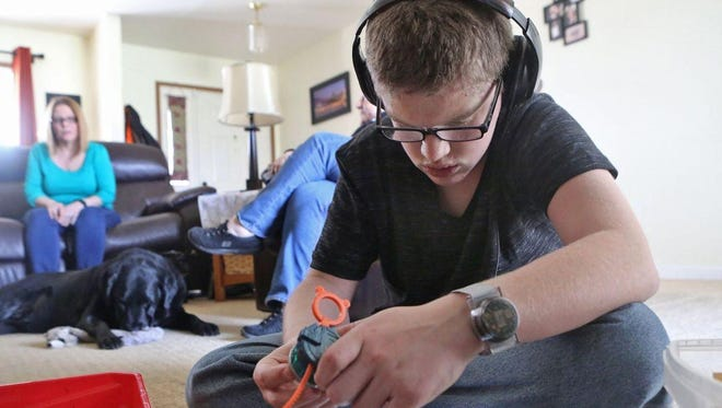 Ryan Delaney, 18, watches a video March 14 in his St. Peter's home. Behind him is his mother, Michelle Delaney. Ryan Delaney wears a Care Trak bracelet that would help locate him if he ever got lost or wandered away from his home.