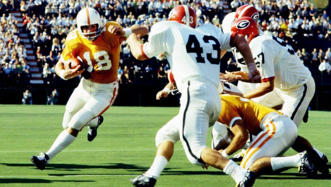 Tennessee quarterback Bubba Wyche runs for yardage as Georgia linebacker Ronnie Huggins closes in during the season opener on Sept. 14, 1968.