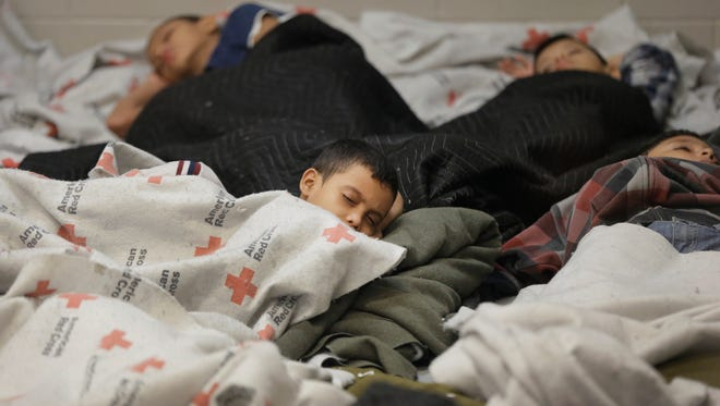 Young detainees sleep in a holding cell June 18, 2014, at a Customs and Border Protection processing facility in Brownsville,Texas.