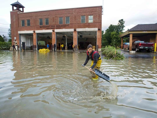 Firefighter Mandy Drake clears a storm drain in front of the Waterbury Fire Department in the wake of tropical storm Irene on Aug. 29, 2011.