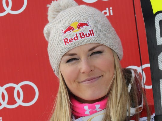 Lindsey Vonn smiles on the podium after winning an alpine ski, women's World Cup super-G, in St. Moritz, Switzerland, Sunday, Jan. 25, 2015. Lindsey Vonn mastered a tricky super-G race on Sunday for a record-extending 64th World Cup victory. (AP Photo/Armando Trovati)