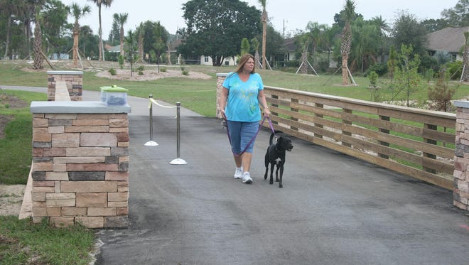 Beverly Schmidt and her dog, Jessa, enjoy a walk soon after the opening of Trailhead Park in Lehigh Acres n 2013. The park fearures a half mile mulit-use trail that could be joined by a bike and pedestrian  trail on the banks of the Abel Canal from Joel Boulevard to Harns Marsh.