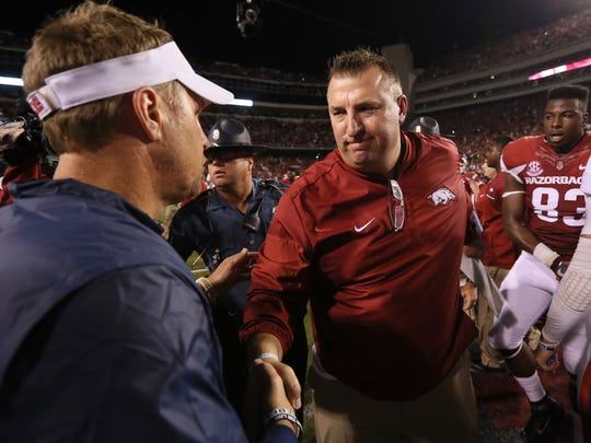 Arkansas Razorbacks head coach Bret Bielema shakes hands with Ole Miss Rebels head coach Hugh Freeze after the game at Donald W. Reynolds Razorback Stadium. Arkansas defeated Ole Miss 34-30.
