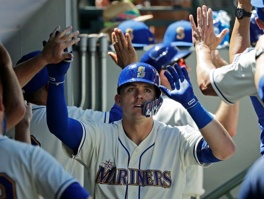 Seattle Mariners' Ryon Healy is greeted in the dugout