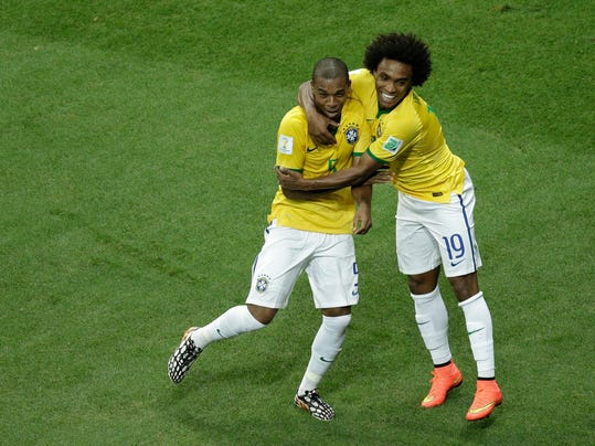Brazil's Fernandinho, left, celebrates scoring his side's 5th goal during the group A World Cup soccer match between Cameroon and Brazil at the Estadio Nacional in Brasilia, Brazil, Monday, June 23, 2014. (AP Photo/Christophe Ena)