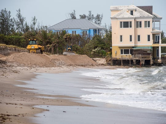 Crews work to build up the dunes at Bathtub Beach in