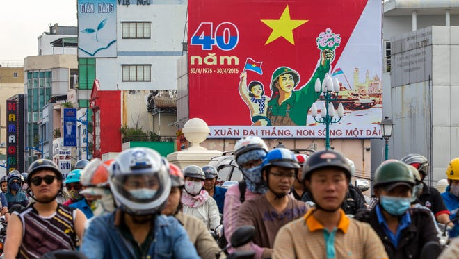 People ride past a billboard marking the 40th anniversary of the end of the Vietnam War, in Ho Chi Minh, Vietnam.