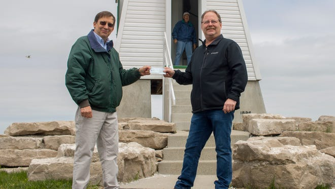 Richard Norgard, left, president of the Port Clinton Lighthouse Conservancy, presents an official $1 check for a year's rent to Port Clinton Mayor Hugh Wheeler.