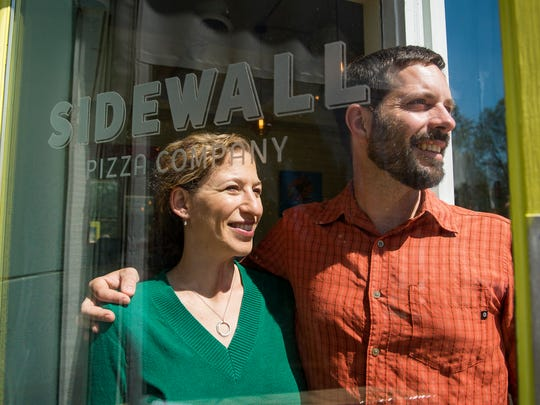 Andy O'Mara and Loren Frant, owners of Sidewall Pizza Co. pose for a portrait next to the entrance of their location on Cleveland Street on Tuesday, April 11, 2017.