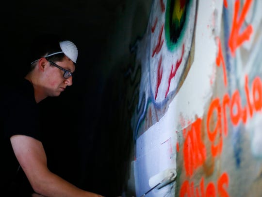 "Alex Johnson paints over an offensive symbols in the ""Acid Tunnel,"" a dark and damp drainage tunnel below the interchange of US 65 and I-44 on Saturday, July 1, 2017."