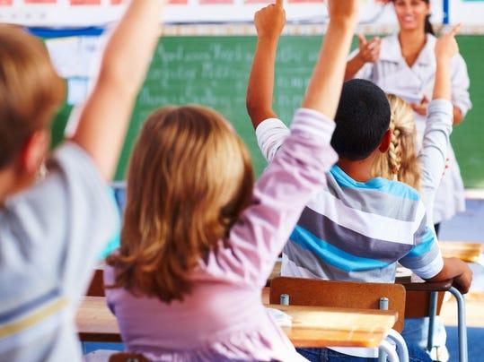 Rear view of school children raising their hands