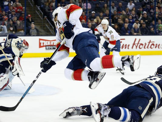 Florida Panthers' Vincent Trocheck, center, jumps over Columbus Blue Jackets' Zach Werenski, right, to shoot the puck against Sergei Bobrovsky, of Russia, during the first period of an NHL hockey game Thursday, March 16, 2017, in Columbus, Ohio. (AP Photo/Jay LaPrete)