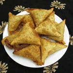 """Savory fried sambusa pastries stuffed with ground beef and vegetables are a favorite snack at the home of Amina Osman, a Somali Bantu refugee profiled in """"Flavors From Home: Refugees in Kentucky Share Their Stories and Comfort Foods,"""" a new book from University Press of Kentucky."""