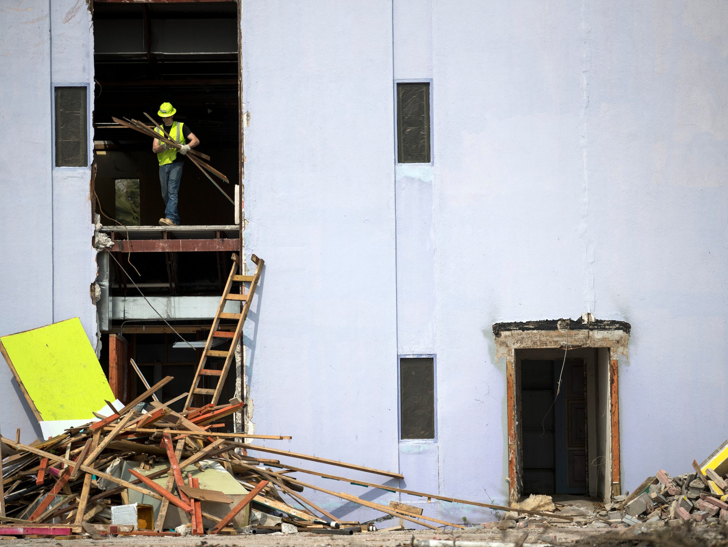 Contractors work to demolish the a building in downtown