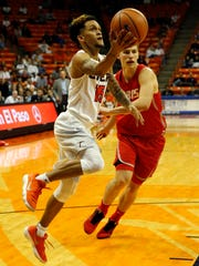 UTEP guard Kobe McGee hangs in the air as he prepared to lay the ball in the basket during first half action in their game Saturday night against the New Mexico Lobos. UNM Lobo Jachai Simmons can just look on.